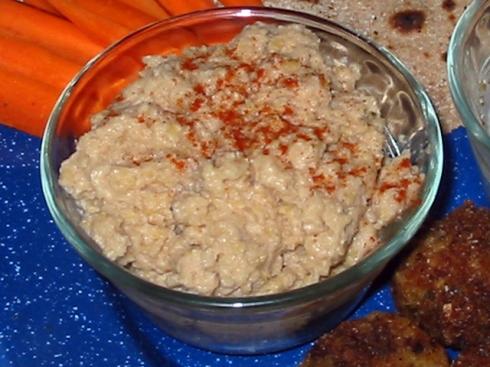 Bowl of prepared hummus sprinkled with paprika